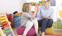 Counselor and child high fiving in a room with toys.